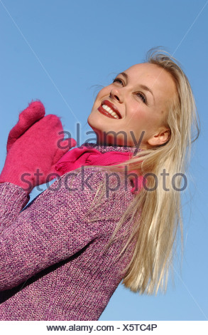 Semi profile of female long blonde hair brown tones of make up wearing purple jumper bright pink scarf and mittens hands - Stock Photo