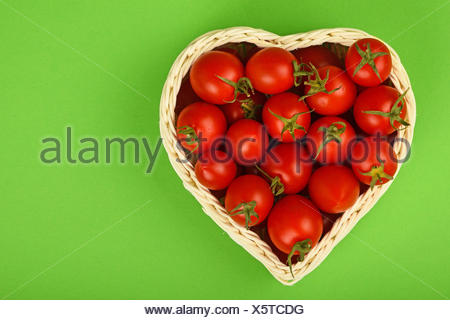 Cherry tomatoes in heart shaped basket on green - Stock Photo