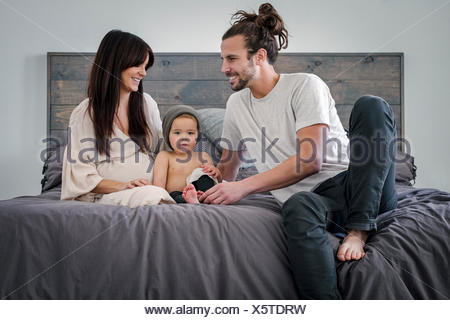 A young couple and their young son sitting together on their bed. - Stock Photo