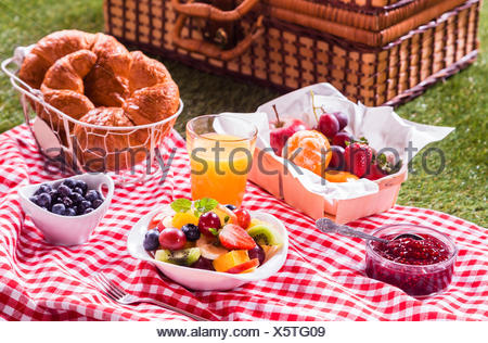 Healthy vegetarian or vegan picnic with a delicious spread of fresh fruit, golden croissants, berry jam and tropical fruit salad on a red and white tablecloth alongside a hamper on green grass - Stock Photo