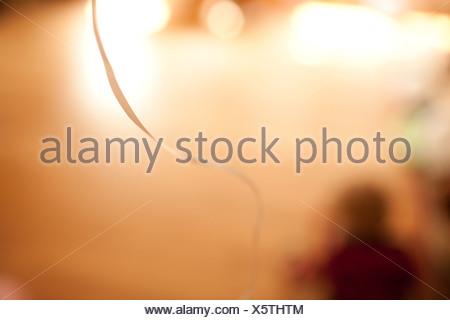 Blurred figure sitting on floor with balloon ribbon - Stock Photo