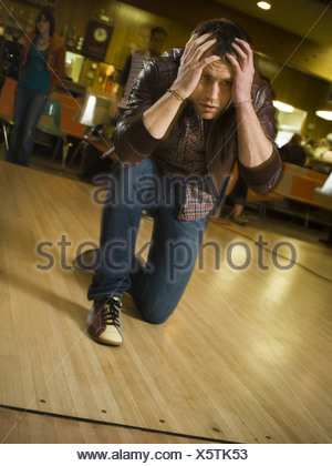 Young man kneeling with his hand on his forehead at a bowling alley - Stock Photo