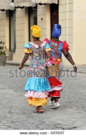 Two Creole women wearing colourful dresses walking in the centre of Havana, Cuba, Greater Antilles, Central America, America - Stock Photo
