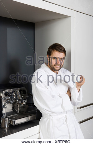 A man in a bathrobe holding a coffee cup - Stock Photo