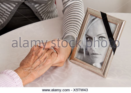 Holding hands for comfort. Grief at death. - Stock Photo