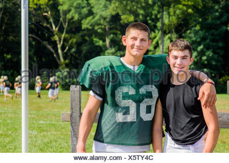 Portrait teenage male American football player with arm around friend at playing field - Stock Photo
