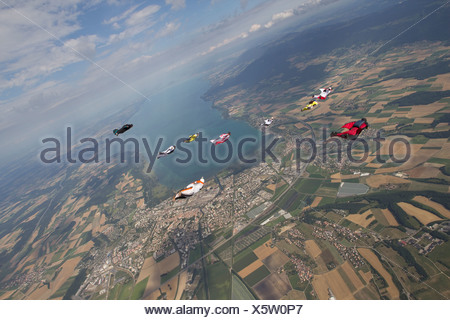 People skydiving over rural landscape - Stock Photo