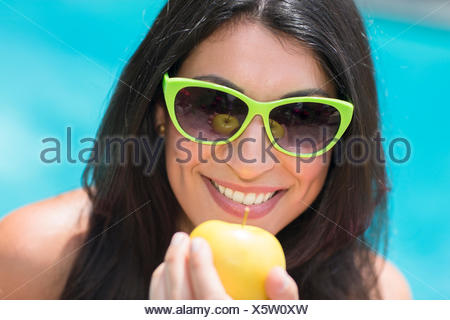 Portrait of young woman by pool holding up apple - Stock Photo