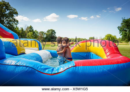 Two boys hugging on an inflatable water slide - Stock Photo