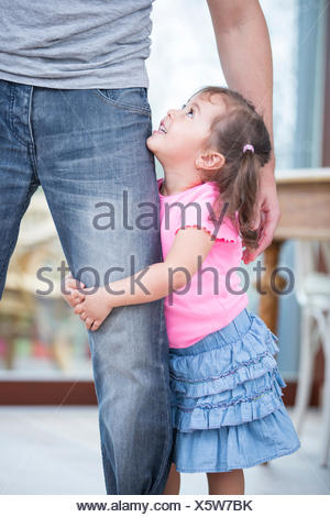 Side view of girl hugging father's leg in house - Stock Photo