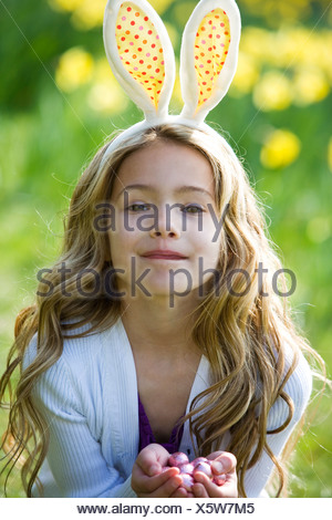 A young girl holding Easter eggs, wearing bunny ears - Stock Photo