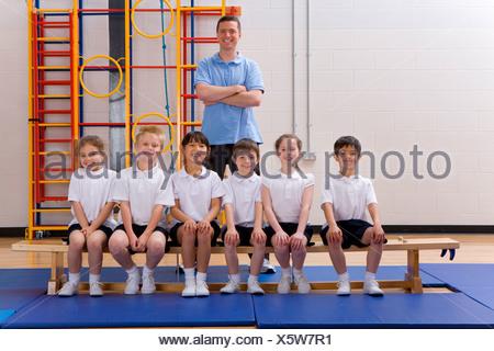 School children and teacher in school gymnasium - Stock Photo