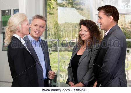 Successful and happy business people standing at office entrance after inspiring business meeting - Stock Photo