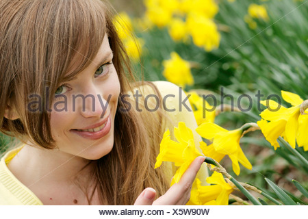 young woman with narcissus in a park - Stock Photo