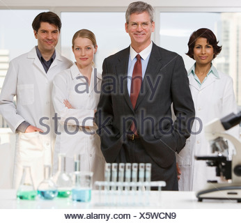 Businessman and scientists in laboratory - Stock Photo