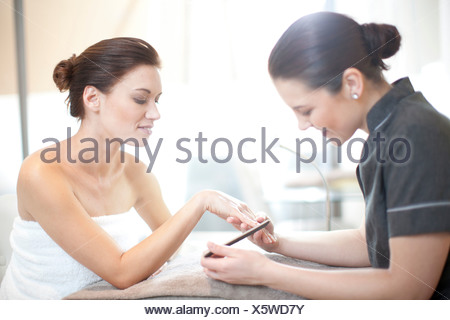 Woman having her nails done in spa treatment room - Stock Photo