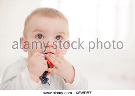 Baby  biting crumpled paper on floor - Stock Photo