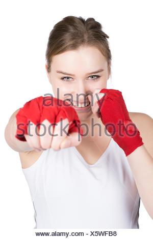 Freigestelltes Foto einer jungen Sportlerin in Box Stellung, die ihre Hände mit einer roten Bandage bandagiert hat. Die Frau lächelt. Gesicht ist scharf. Hand liegt im Unschärfebereich. - Stock Photo