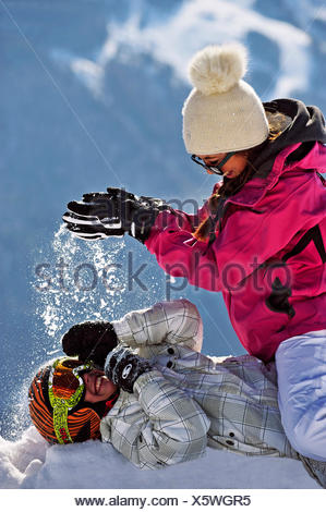 two teenagers doing a snowball fight, France - Stock Photo