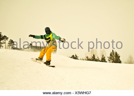 Young man snow boarding on mountain - Stock Photo