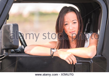 Portrait of young woman in car - Stock Photo