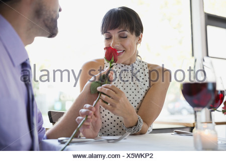 Thoughtful man giving woman rose in restaurant - Stock Photo