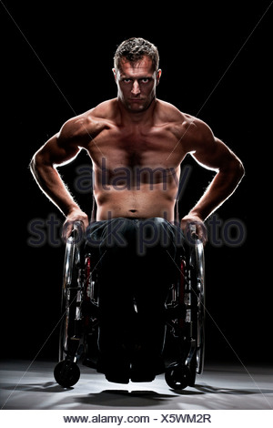 Muscular wheelchair user with a bare chest, Innsbruck, Tyrol, Austria - Stock Photo
