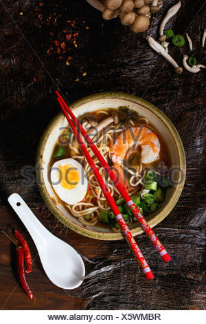 Ceramic bowl of asian ramen soup with shrimp, noodles, spring onion, sliced egg and mushrooms, served with red chopsticks and ch - Stock Photo