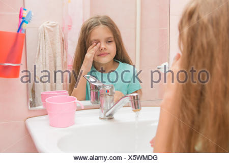 Girl wet hand wipes the sleep from his eyes in the bathroom - Stock Photo