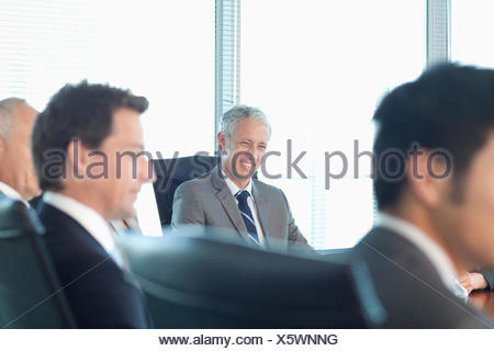 Business people watching presentation in conference room - Stock Photo
