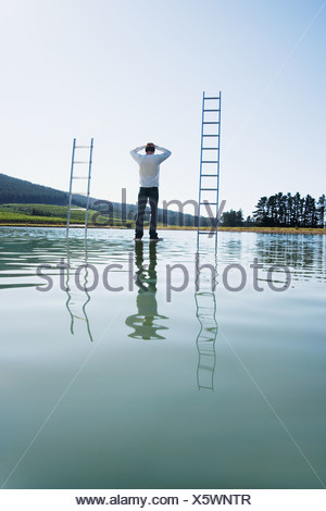 Man standing on water with ladders - Stock Photo