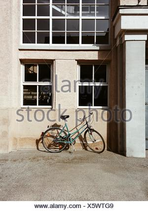 Side View Of A Bicycle Parked Against Wall - Stock Photo