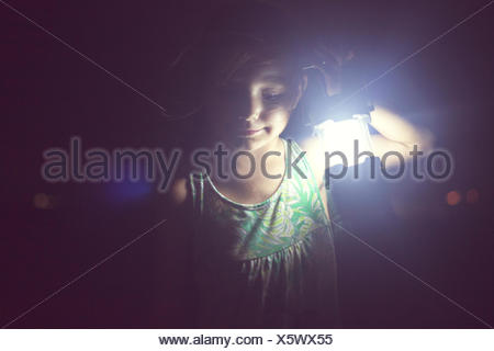 Girl holding lamp in the darkness - Stock Photo