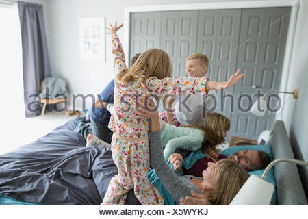 Playful children in pajamas jumping on parents in bed - Stock Photo