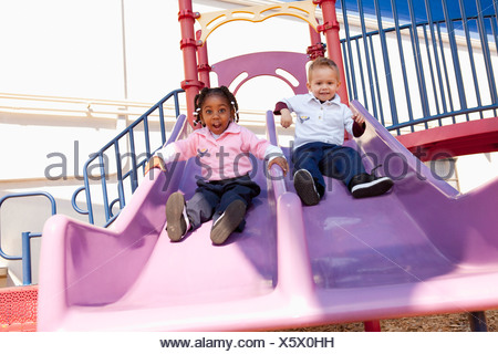 Fort Lauderdale, Florida, United States Of America; Two Young Children Going Down The Slide At The Playground - Stock Photo