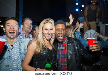 Portrait of enthusiastic friends drinking in nightclub - Stock Photo