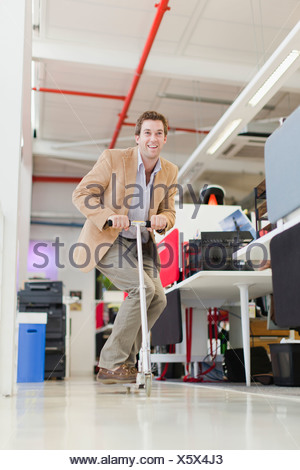 Businessman riding scooter in office - Stock Photo