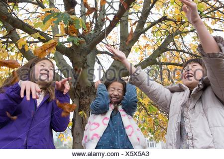 Three young girls throwing autumn leaves in air - Stock Photo
