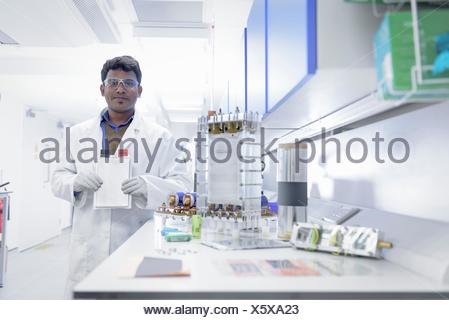Portrait of scientist assembling lithium ion battery samples in battery research facility - Stock Photo
