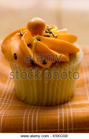 Muffin with orange cream topping FoodCollection - Stock Photo