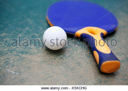 Table tennis paddle and ball on worn table - Stock Photo