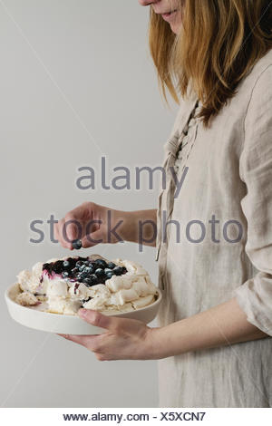 Woman tasting cake. Homemade meringue cake Pavlova with whipped cream, sugar powder, fresh blueberries and blueberry sauce in female hands over gray w - Stock Photo