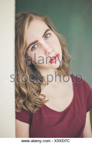 Portrait of a girl leaning against a wall - Stock Photo