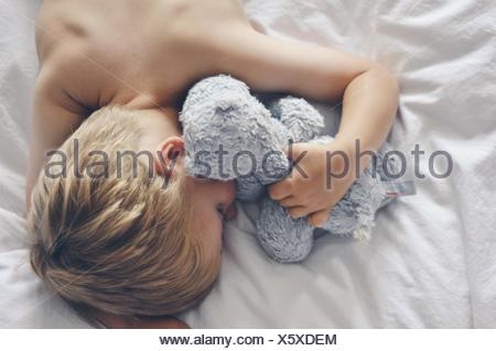 Overhead view of boy sleeping in bed with teddy bear - Stock Photo