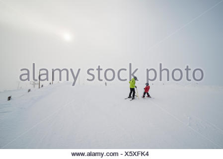 Finland, Lapland, Levi, Grandfather and grandson (6-7) skiing - Stock Photo