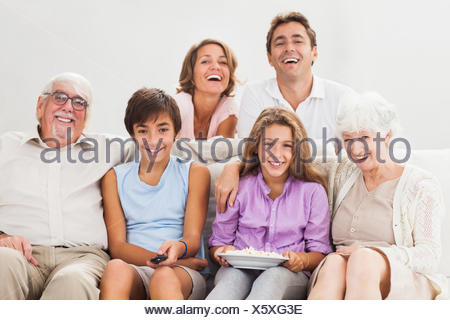 Multigeneration family on couch watching tv - Stock Photo