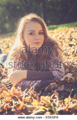 Portrait of teenage girl lying on the ground covered with autumn foliage - Stock Photo
