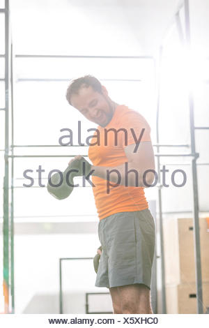 Confident man lifting kettlebell in crossfit gym - Stock Photo