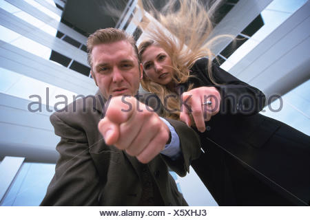 Business man and woman leaning over - Stock Photo