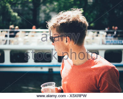 Man Wearing Sunglasses While Standing By Canal - Stock Photo